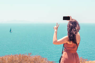 Beautiful girl in a dress takes a selfie on the background of the sea and a sailing boat