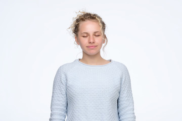 Calm young caucasian girl with curly hair standing with closed eyes with slight smile. Studio shot