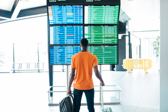 Rear view of man looking at arrival and departure board in airport