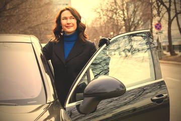 beautiful businesswoman near car