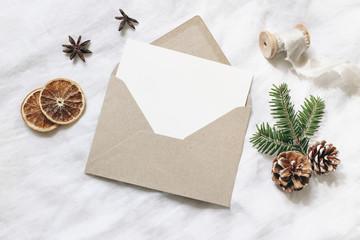 Christmas blank greeting card mock-up scene. Festive winter wedding composition. Craft envelope,...