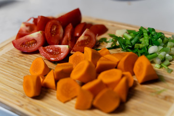 Cut  Fresh Mixed Vegetables on Chopping Board - Carrot, Tomatoes, Spring Onions