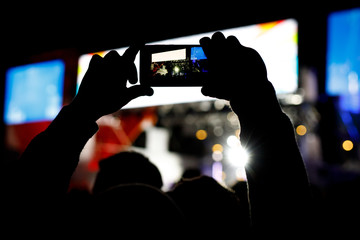 Silhouette of people with smartphones in hands at a music concert in front of stage lights.