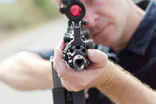 Closeup of a man aiming an assault rifle with scope.