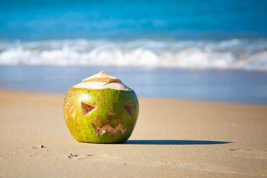 Green coconut with a face carved on it, like a halloween pumpkin. Lies in the sand on a tropical beach on a background of waves. Holiday trip concept.