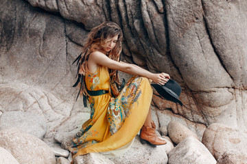 beautiful young boho style model on the stone beach