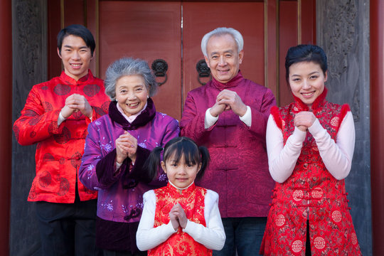Family dressed in holiday attire in front of house