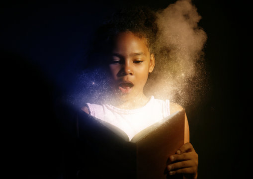 Surprised African-American girl reading magic book on dark background