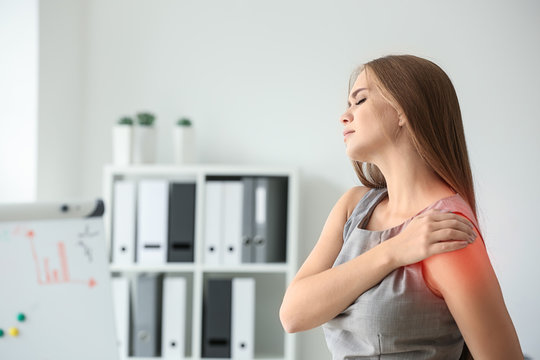 Young woman suffering from pain in shoulder at workplace