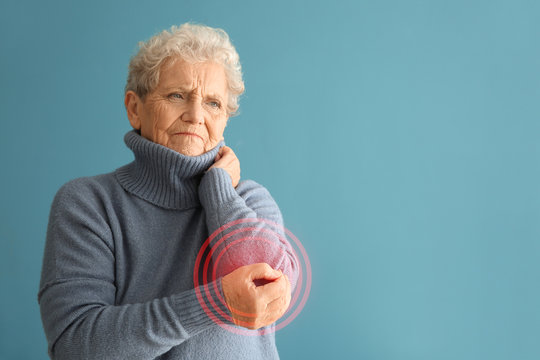 Senior woman suffering from pain in elbow on color background