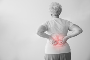 Senior woman suffering from back pain on light background