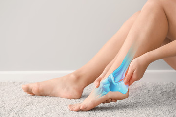 Woman suffering from pain in foot while sitting on carpet