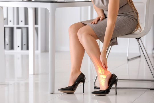 Young woman suffering from leg pain because of uncomfortable shoes in office