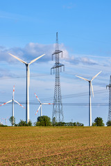 An electricity pylon and wind energy generators seen in Germany