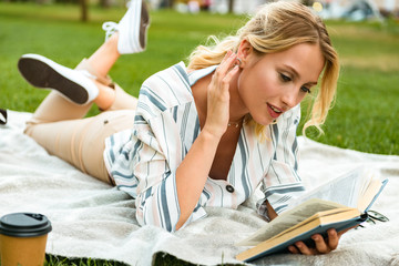 Beautiful young blonde girl relaxing on a lawn at the park
