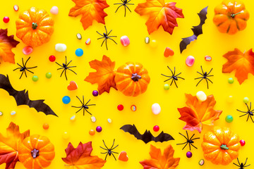 Bright Halloween composition with sweets, bats and pumpkins on yellow background top view pattern Fototapete