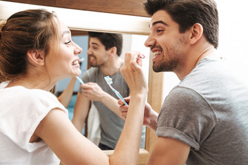 Image of beautiful couple cleaning teeth together in bathroom