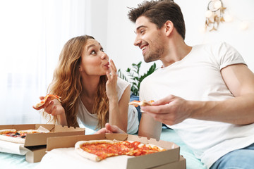 Image of lovely happy couple lying on bed at home and eating pizza