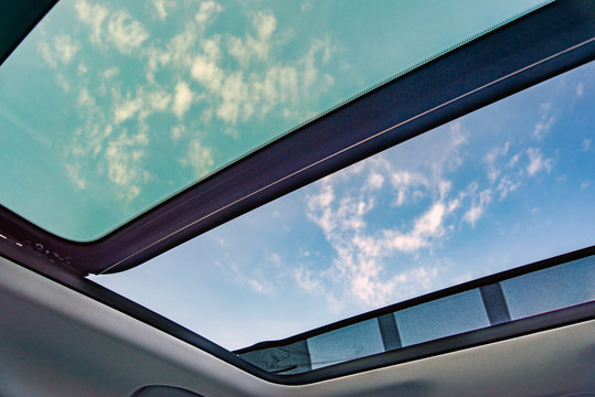Blue sky through an open car sunroof , view from the passenger compartment,open sunroof look up to sky..