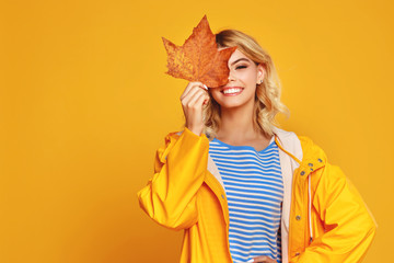 happy emotional girl with autumn leaves on colored yellow background.