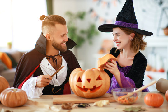 couple of people are preparing for Halloween in costumes of witch and vampire with pumpkins.