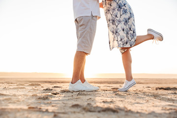 Cropped photo of beautiful caucasian couple kissing and hugging while walking on sunny beach