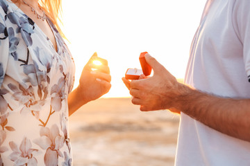 Cropped photo of romantic man making proposal to his girlfriend with ring while walking on sunny beach
