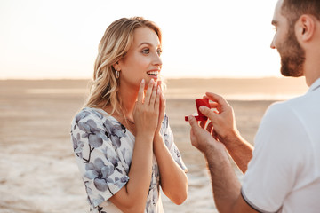 Photo of romantic man making proposal to his amazed woman with ring while walking on sunny beach