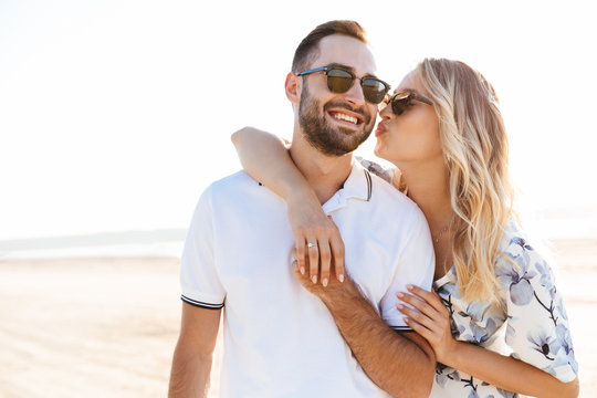 Photo of blonde young woman kissing and hugging handsome man while walking on sunny beach
