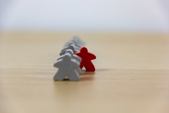 Gray gaming pieces and a red meeple, diversity concept