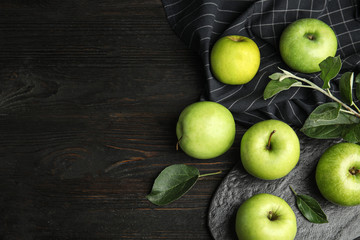 Flat lay composition of fresh ripe green apples on black wooden table, space for text Wall mural
