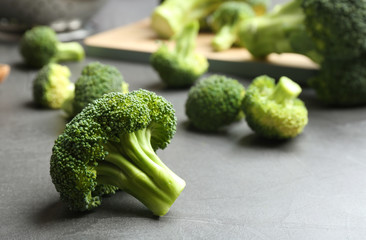 Fresh green broccoli florets on grey table, closeup. Space for text