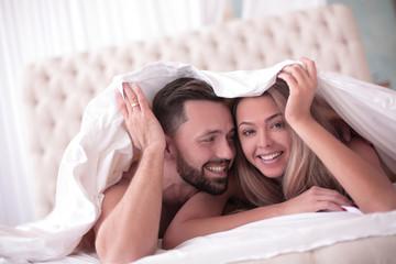 cute loving couple lying under the blanket