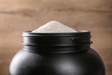 Black jar full of protein powder on brown background, closeup