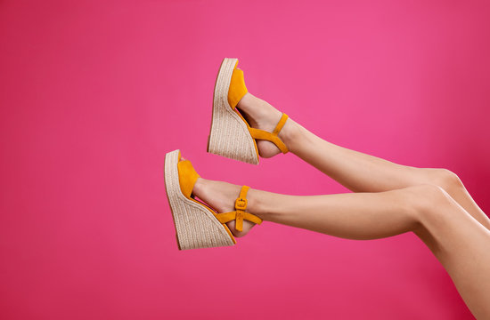 Woman in stylish shoes on pink background