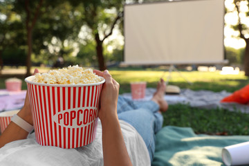 Woman with popcorn watching movie in open air cinema, closeup. Space for text