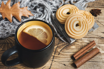 Autumn still life with cup of tea, cookies, sweater and leaves on wooden background. concept of cozy autumn, fall season