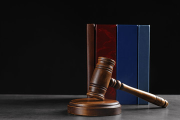 Judge's gavel and books on grey table against black background, space for text. Criminal law concept