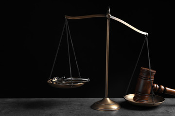 Judge's gavel and scales on grey table against black background. Criminal law concept
