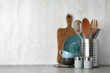 Different kitchen utensils on grey table against light background. Space for text