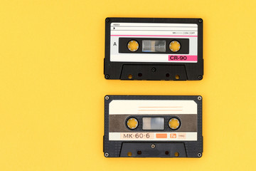 Old audio tape cassettes on a bright yellow background. Top view, old technology concept
