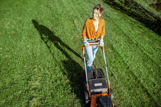 Beautiful young woman cutting grass with gasoline lawn mower, gardening on the backyard in the countryside, view from above