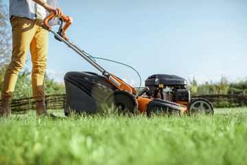 Man cutting grass with gasoline lawn mower on the backyard, cropped image with no face