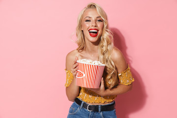 Image of happy woman smiling and holding popcorn bucket