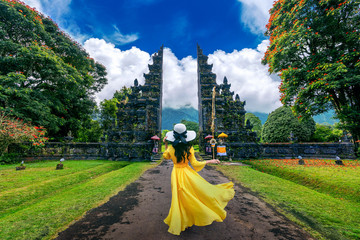 Woman walking at big entrance gate, Bali in Indonesia.