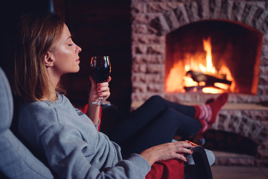 Cozy home. Close up of young woman drinking red wine near the fireplace.