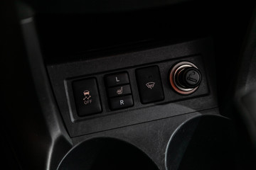 Close up of a cigarette lighter,Seat heating indicator , off road buttons. modern car interior.