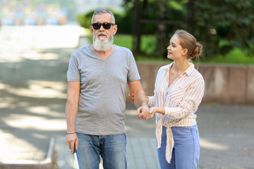 Woman helping blind mature man to cross road