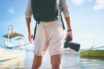Photography and travel. Close up of young man holding camera enjoying beautiful sea view on fishing beach.
