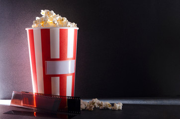 Bucket of salty popcorn and film stock against dark background.Darkness at the cinema